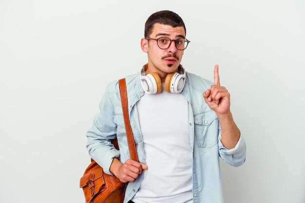 Uomo giovane studente caucasico ascoltando musica isolato su sfondo bianco con qualche grande idea, il concetto di creatività.