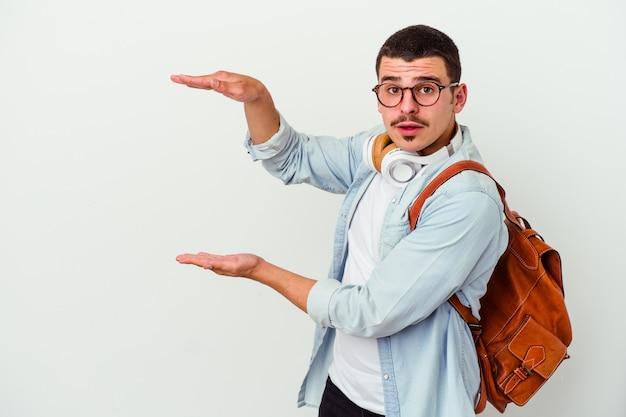 Uomo giovane studente caucasico ascoltando musica isolato su sfondo bianco scioccato e stupito in possesso di uno spazio di copia tra le mani.