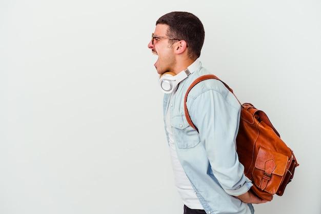 Uomo giovane studente caucasico che ascolta la musica isolata su priorità bassa bianca che grida verso uno spazio della copia