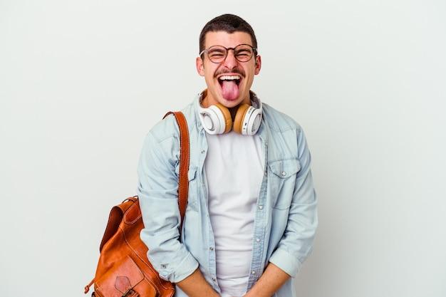 Uomo giovane studente caucasico che ascolta la musica isolata sulla parete bianca divertente e amichevole che attacca fuori la lingua.
