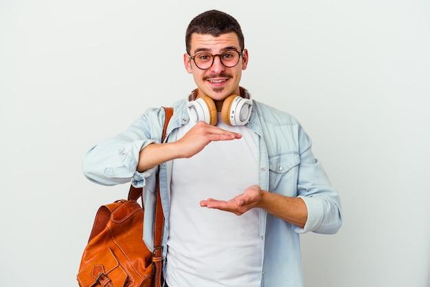 Uomo giovane studente caucasico che ascolta la musica isolata sulla parete bianca che tiene qualcosa con entrambe le mani, presentazione del prodotto.