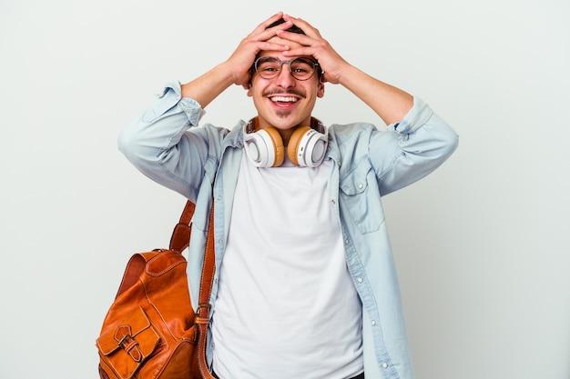 L'uomo giovane studente caucasico che ascolta la musica isolata sulla parete bianca ride con gioia mantenendo le mani sulla testa. concetto di felicità.