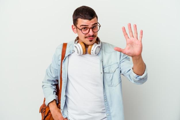 Uomo giovane studente caucasico che ascolta la musica isolata sul muro bianco sorridente che mostra allegro numero cinque con le dita.