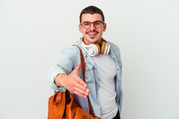 Uomo giovane studente caucasico che ascolta la musica isolata sulla parete bianca che allunga la mano nel gesto di saluto.