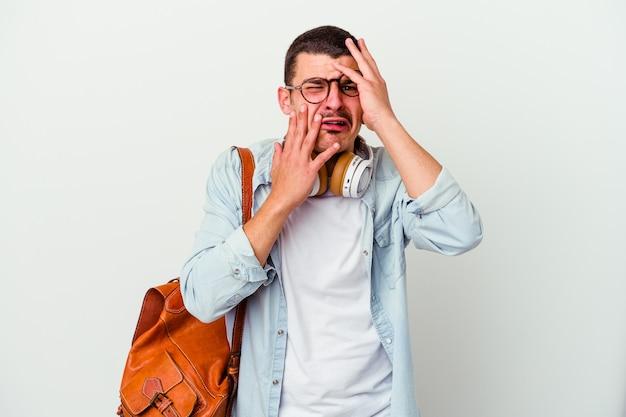 Uomo giovane studente caucasico ascoltando musica isolata sul muro bianco piagnucolando e piangendo sconsolato.