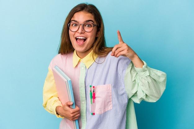 Giovane donna caucasica dello studente che tiene libri isolati su fondo blu che ha un'idea, concetto di ispirazione.