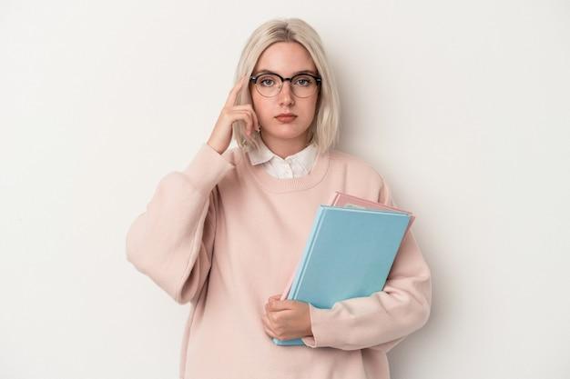 Giovane studentessa caucasica che tiene libri isolati su sfondo bianco che punta il tempio con il dito, pensando, focalizzato su un compito.