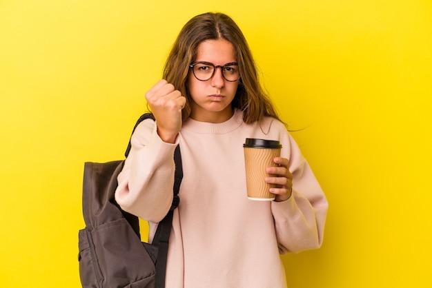 Giovane studentessa caucasica che tiene il caffè isolato su sfondo giallo che mostra il pugno alla telecamera, espressione facciale aggressiva.