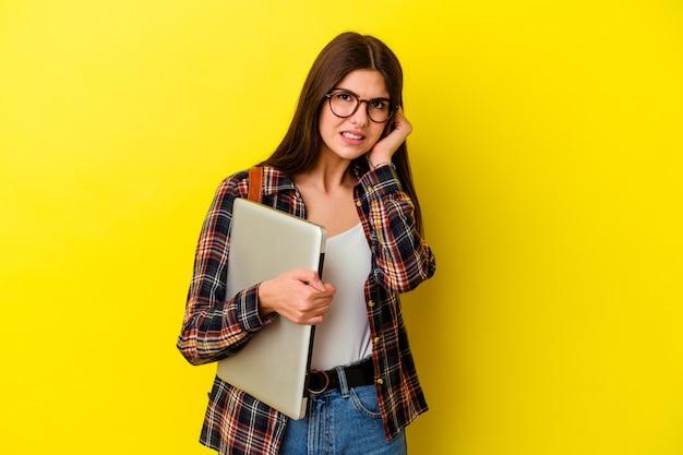 Giovane donna caucasica dell'allievo che tiene un computer portatile isolato sulle orecchie rosa della copertura murale con le mani.