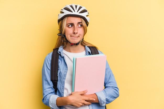 Giovane studentessa caucasica che indossa un casco da bici isolato su sfondo giallo confuso, si sente dubbiosa e insicura.