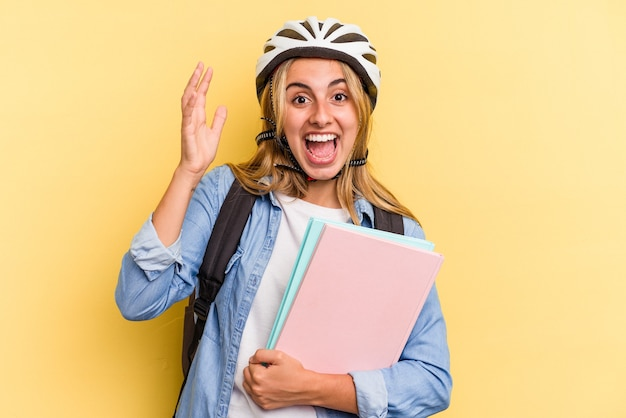 Giovane studentessa caucasica che indossa un casco da bici isolato su sfondo giallo riceve una piacevole sorpresa, eccitata e alzando le mani.