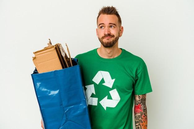 Cartone riciclato giovane uomo caucasico tatuato isolato su sfondo bianco, sognando di raggiungere obiettivi e scopi