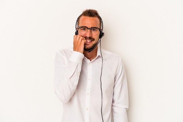Giovane uomo caucasico telemarketer con tatuaggi isolati su sfondo bianco che si morde le unghie, nervoso e molto ansioso.