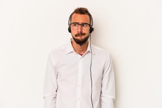 Il giovane uomo caucasico di telemarketing con tatuaggi isolati su sfondo bianco confuso, si sente dubbioso e insicuro.
