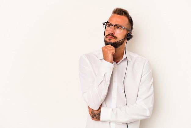 Giovane uomo caucasico telemarketer con tatuaggi isolati su sfondo bianco guardando lateralmente con espressione dubbiosa e scettica.