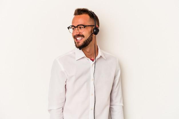 Il giovane uomo caucasico del telemarketer con i tatuaggi isolati su fondo bianco guarda da parte sorridente, allegro e piacevole.