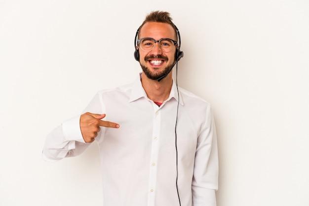 Giovane uomo caucasico telemarketer con tatuaggi isolato su sfondo bianco persona che punta a mano a uno spazio copia camicia, orgoglioso e fiducioso