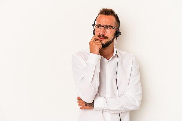 Giovane uomo caucasico telemarketer con tatuaggi isolati su sfondo bianco rilassato pensando a qualcosa guardando uno spazio di copia.