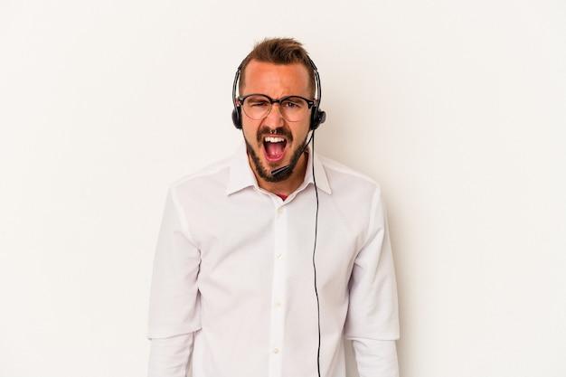 Giovane uomo caucasico telemarketer con tatuaggi isolati su sfondo bianco urlando molto arrabbiato e aggressivo.