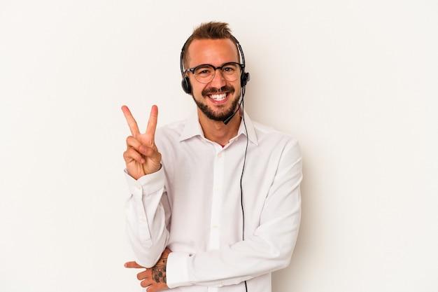 Giovane uomo caucasico telemarketer con tatuaggi isolati su sfondo bianco che mostra il numero due con le dita.