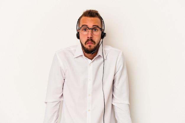 Il giovane uomo caucasico del telemarketer con i tatuaggi isolati su fondo bianco alza le spalle e apre gli occhi confusi.