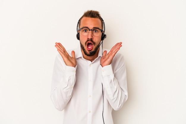 Giovane uomo caucasico telemarketer con tatuaggi isolati su sfondo bianco sorpreso e scioccato.