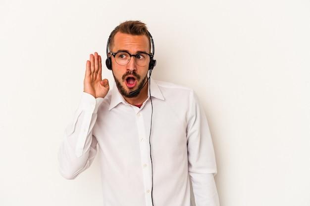 Giovane uomo caucasico telemarketer con tatuaggi isolati su sfondo bianco cercando di ascoltare un pettegolezzo.