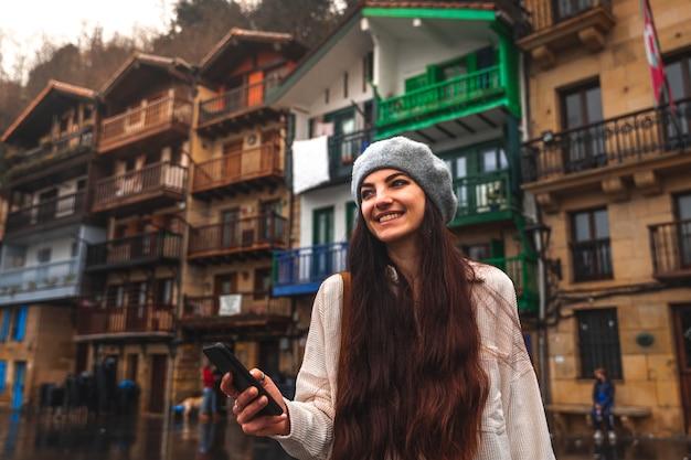 Giovane donna caucasica turistica utilizzando lo smartphone in una vecchia città.