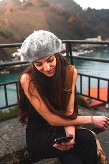 La giovane donna caucasica turistica che utilizza lo smartphone si è seduta su una panchina vicino al mare.