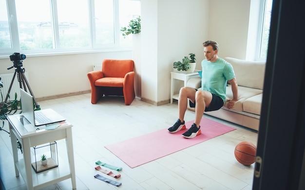 Giovane istruttore caucasico facendo esercizi di fitness a casa con un tutorial online utilizzando fotocamera e laptop