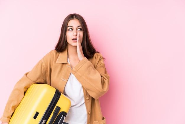 La giovane donna caucasica del viaggiatore che tiene una valigia sta dicendo le notizie di una frenata calde segrete e sta guardando da parte