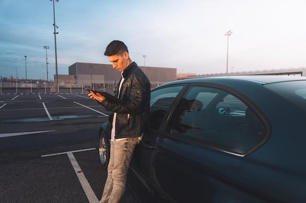 Giovani caucasici utilizzando una tavoletta digitale con un'auto sportiva dietro in un parcheggio.