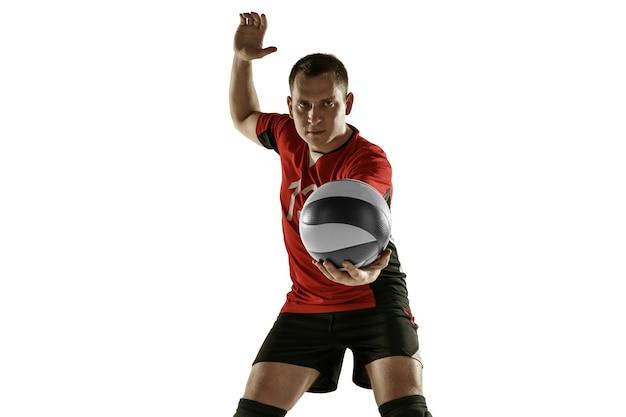 Giovane placticing caucasico del giocatore di pallavolo isolato sulla parete bianca. allenamento sportivo maschile con la palla in movimento e azione. sport, stile di vita sano, attività, concetto di movimento. copyspace.