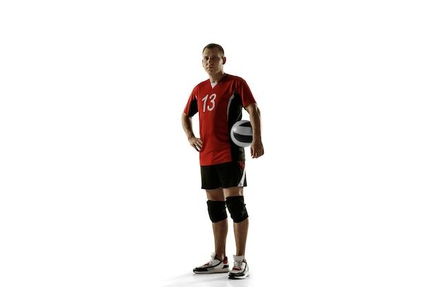 Giovane giocatore di pallavolo caucasico che placa sul muro bianco. sportivo maschio in posa fiducioso con la palla, preparato per la vittoria. sport, stile di vita sano, attività, concetto di movimento. copyspace.