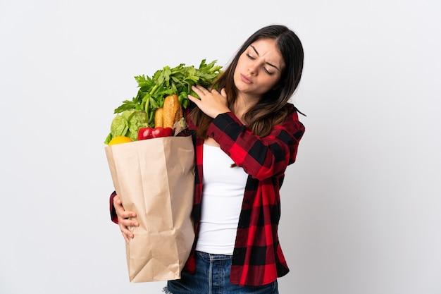 Giovani caucasici con verdure isolate su bianco che soffrono di dolore alla spalla per aver fatto uno sforzo