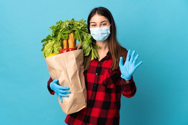 Giovane caucasico con verdure e maschera isolata sulla parete blu che saluta con la mano con l'espressione felice