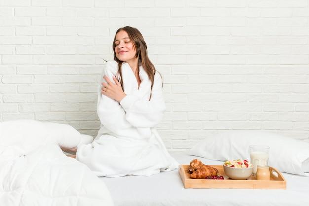 Giovane donna caucasica sugli abbracci del letto, sorridente spensierata e felice.