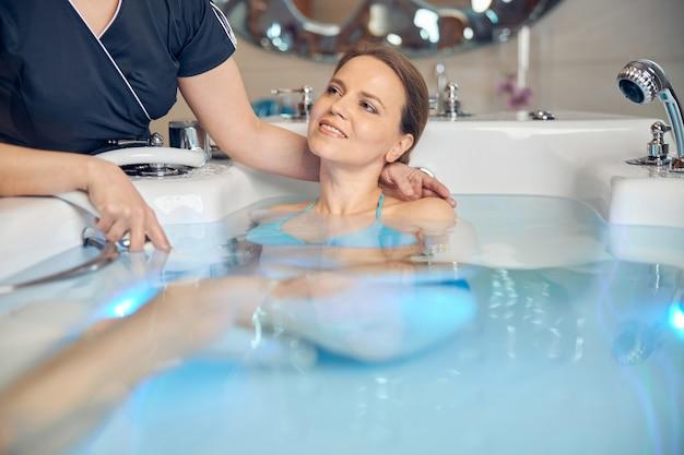 Giovane donna caucasica in bikini sdraiata pacificamente nell'acqua durante la procedura termale