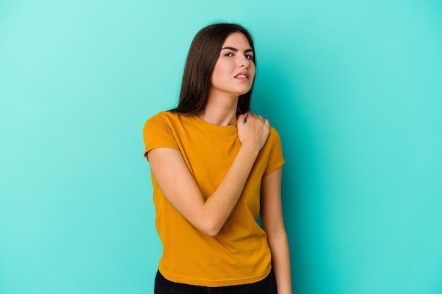 Giovane donna caucasica sull'azzurro che ha un dolore alla spalla.