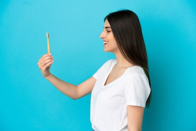 Giovane donna caucasica lavarsi i denti isolati su sfondo blu con felice espressione