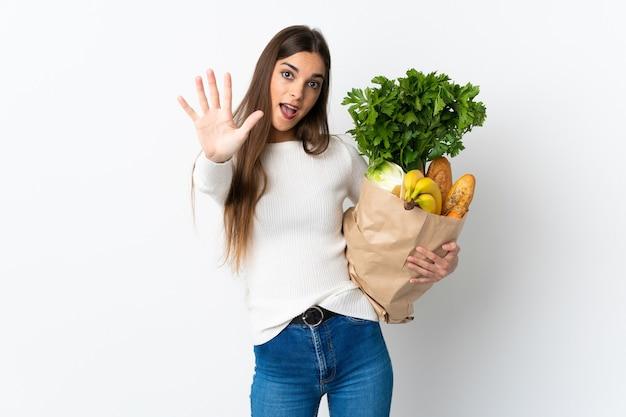 Giovane donna caucasica che compra del cibo isolato sul muro bianco contando cinque con le dita