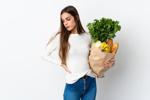 Giovane donna caucasica che compra del cibo su bianco che soffre di mal di schiena per aver fatto uno sforzo