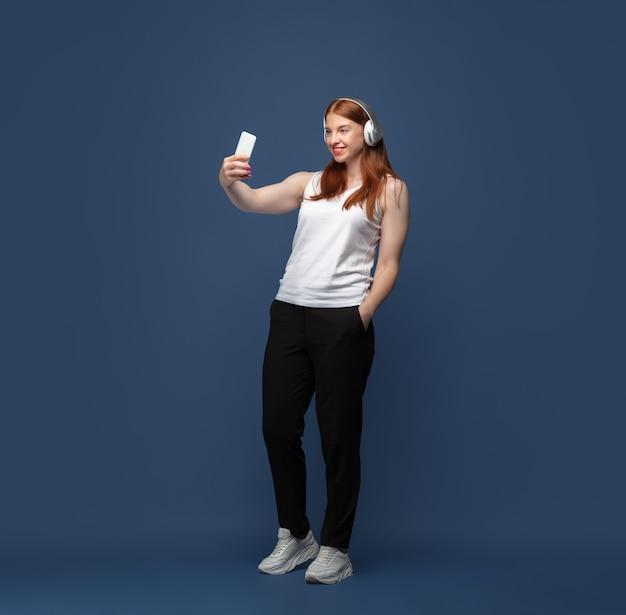 Giovane donna caucasica in abbigliamento casual che fa foto selfie