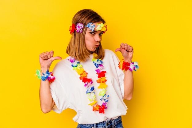 La giovane donna caucasica che celebra una festa hawaiana isolata su giallo si sente orgogliosa e sicura di sé, esempio da seguire.