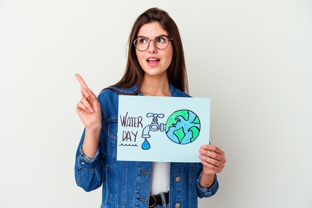 Giovane donna caucasica che celebra la giornata mondiale dell'acqua isolata sul rosa con un'idea, un concetto di ispirazione.