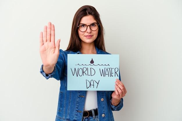 La giovane donna caucasica che celebra la giornata mondiale dell'acqua isolata sul rosa sta dicendo una notizia segreta di frenata calda e sta guardando da parte