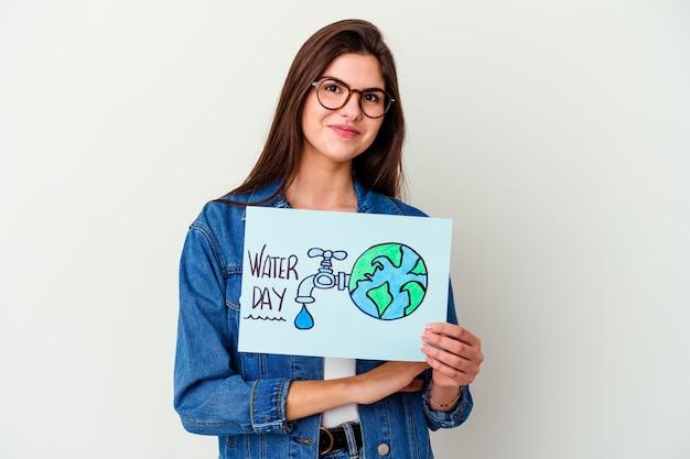 Giovane donna caucasica che celebra la giornata mondiale dell'acqua isolata sul rosa mantenendo un segreto o chiedendo silenzio.