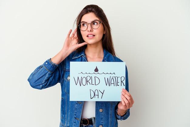 Giovane donna caucasica che celebra la giornata mondiale dell'acqua isolata sul rosa che mostra uno spazio di copia su una palma e che tiene un'altra mano sulla vita.