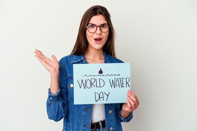 Giovane donna caucasica che celebra la giornata mondiale dell'acqua isolata sul rosa sorridendo e indicando da parte, mostrando qualcosa in uno spazio vuoto.