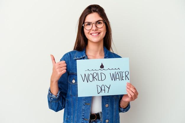 Giovane donna caucasica che celebra la giornata mondiale dell'acqua isolata sul rosa sorridendo e alzando il pollice